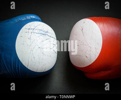 Old and used boxing gloves on dark background. - Stock Photo