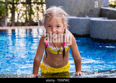 little girl in a yellow swimsuit in a blue pool like a mermaid. kids concept, kids fashion. - Stock Photo