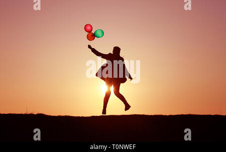 girl jumping with balloons at sunset, colorful balloons, incredible sunset sky flying into the sky - Stock Photo