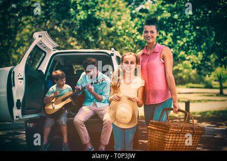Portrait of mother and daughter standing with picnic basket while father and son playing guitar in b - Stock Photo
