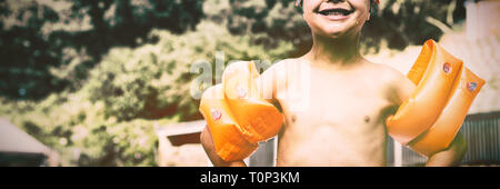 Boy wearing arm bands standing at poolside - Stock Photo