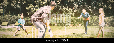 Happy family playing cricket in park - Stock Photo