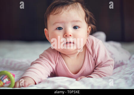 Closeup portrait of cute adorable Asian mixed race baby girl four months old lying on her tummy looking in camera. Natural face expression. Childhood