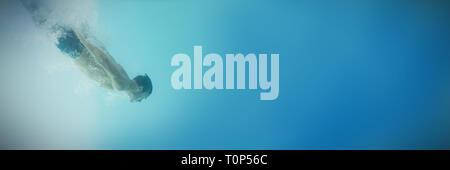 Shirtless man swimming underwater - Stock Photo