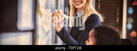 Portrait of teacher assisting schoolboy on whiteboard in classroom - Stock Photo