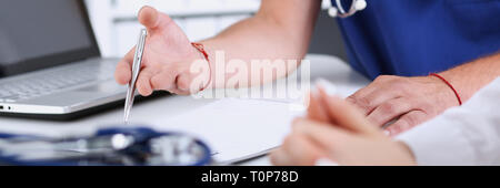 Male doctor arm hold silver pen filling patient complaints - Stock Photo