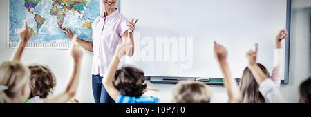 Teacher teaching kids in classroom - Stock Photo