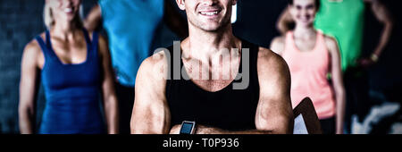 Portrait of smiling gym trainer holding clipboard - Stock Photo