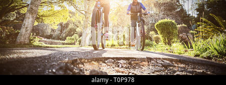 Low angle view of biker couple cycling on countryside road - Stock Photo