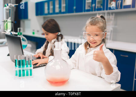 Two little kids in lab coat learning chemistry in school laboratory. Young scientists in protective glasses making experiment in lab or chemical cabin - Stock Photo