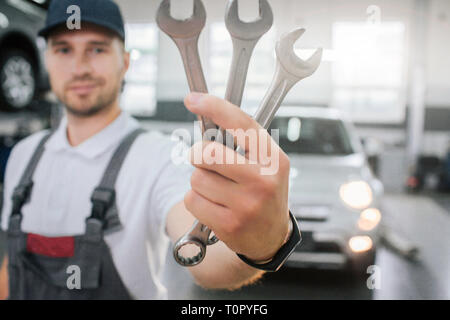 Young handsome man shows set of wrenches. He looks at them and smile. Guy wears uniform. He stands in front of white car. Young man smiles a bit - Stock Photo