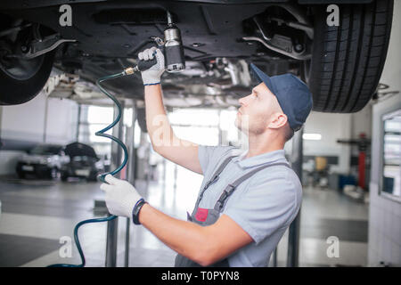 Picture of younf man standing and working underneath car. He looks up. Guy holds and uses drill. He works in white gloves - Stock Photo