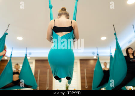 Woman doing fly yoga stretching exercises in hammock. Fit and wellness lifestyle. - Stock Photo