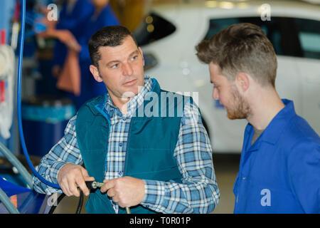 apprentice mechanics working in auto repair shop - Stock Photo