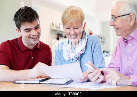 Young Man Helping Senior Couple With Financial Paperwork At Home