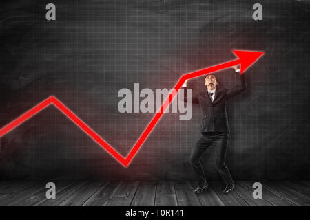 Businessman in black suit holding red arrow going up in room woth wooden floor near black graph ruled balckboard background. - Stock Photo