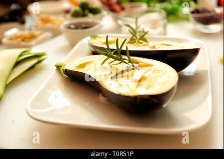 Eine zum Grillen vorbereitete Aubergine die eingeoelt wunde und mit einem frischen Rosmarinzweig belegtwurde liegt auf einer weissen Porzelanschale - Stock Photo