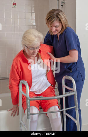 A senior retired woman patient in the Rehabitation Department in a hospital receiving Occupational Therapy from a therapist learning to use a walker. - Stock Photo