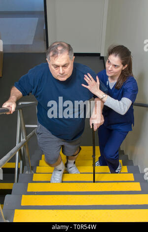 A retired man patient in the Rehabitation Department in a hospital receiving Occupational Therapy from a therapist helping him climb stairs. - Stock Photo
