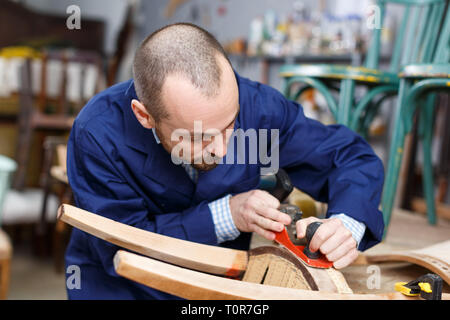 Professional carpenter engaged in restoring antique furniture using instruments - Stock Photo