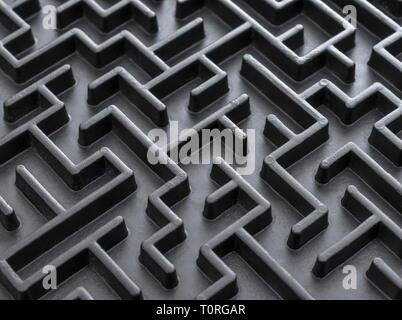 Macro shot of small toy maze painted black. Metaphor for complex, getting lost, navigating, problem solving, unreachable goals, Brexit talks. - Stock Photo