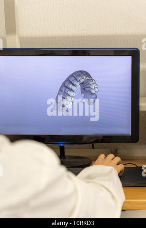 Woman working on computer with dental software platform - Stock Photo