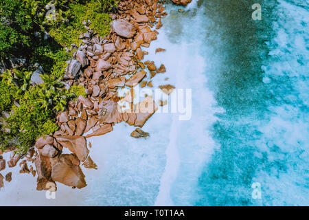 Seychelles La Digue Island. Aerial top view of ocean waves hitting huge bizarre granite rocks on the tropical beach anse cocos with turquoise azure - Stock Photo