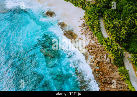 Seychelles Mahe island aerial drone landscape of coastline paradise sandy beach with palm trees and beautiful clear blue ocean waves rolling against