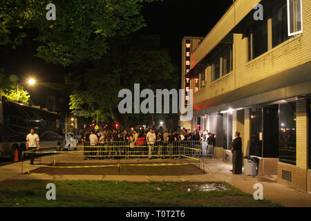 A crowd of concert goers are shown standing in line getting ready to enter the Webster Theater for a concert performance. - Stock Photo