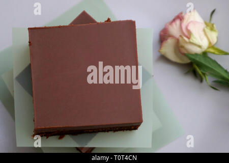 Homemade tasty brownie cake with dark chocolate cover. Stacked chocolate bars on plate - Stock Photo