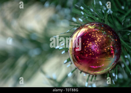 A colorful bulb on the Christmas tree with bokeh effect. - Stock Photo