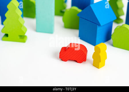 Wooden person with a car on the street of City with wooden blocks houses on the background. Image use for business or insurance concept - Stock Photo
