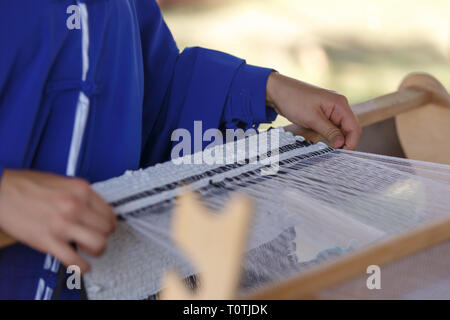 Young woman weaves a white cloth on a hand wood loom - Stock Photo