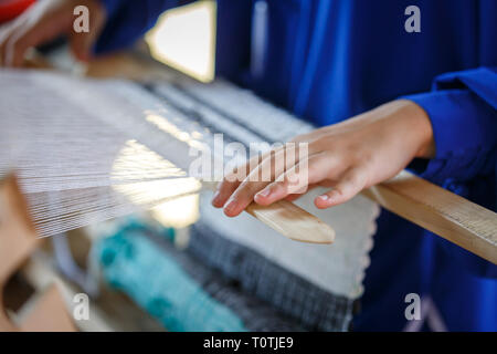 Hands of woman weaving fabric on a wooden loom. Traditional Russian folk art - Stock Photo