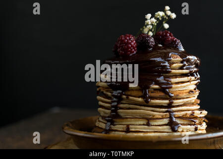 Homemade Pancake with raspberries and chocolate on a black background - Stock Photo