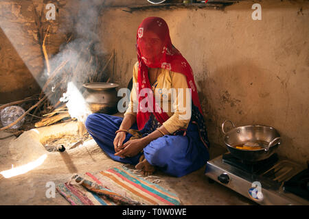 A veiled Muslim woman sits in her house by the fire. Kakani village, Jodhpur, Rajasthan, India. - Stock Photo