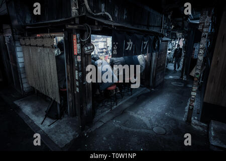 Evening in Omoide Yokocho, Shinjuku, Tokyo. Customers sit at a run down bar in a narrow alley. - Stock Photo