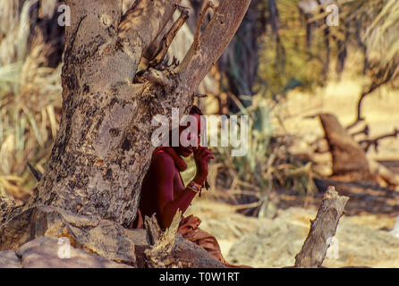 Joking young himba hides to avoid being photographed near the Epupa Falls in Namibia - Stock Photo
