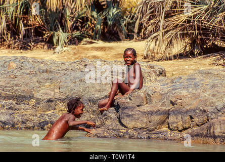 Himba children play in the Kunene river near the Epupa Falls in Namibia - Stock Photo