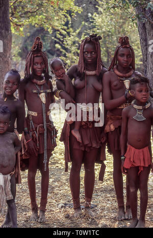 Group of young women and children of the Himba ethnic group near the Epupa Falls on the Kunene River in Namibia, border with Angola - Stock Photo