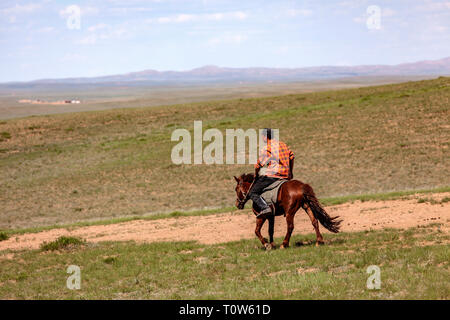 Horse and rider at the Gegentala grasslands north of Hohhot in Inner Mongolia, China. - Stock Photo