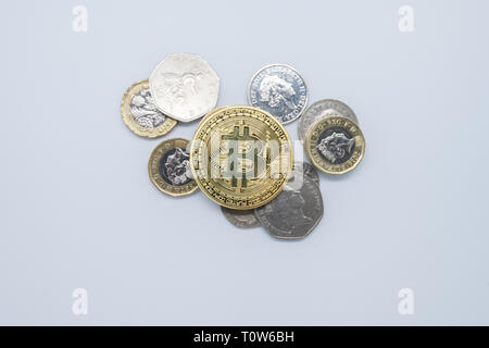 Physical gold Bitcoin laying on top of plain old English money - Stock Photo