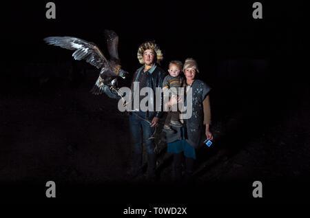bayan Ulgii, Mongolia, 30th September 2015: family of mongolian kazakh eagle hunters at night - Stock Photo