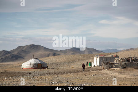 bayan Ulgii, Mongolia, 30th September 2015: mongolian kazakh nomad home in a landscape of Western Mongolia, woman walking outside her home - Stock Photo