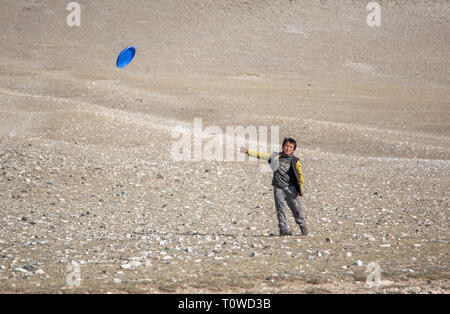 bayan Ulgii, Mongolia, 30th September 2015: mongolian kazakh nomad boy playing frisbee - Stock Photo