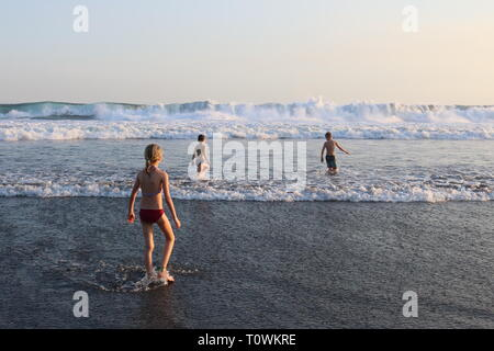 Three children playing in the surf during sunset on a beach in El Salvador Stock Photo