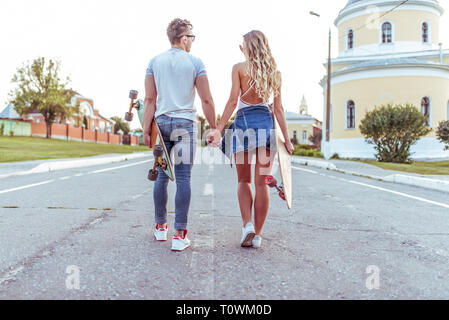 A young couple girl guy are walking summer city, view from rear. In hands of skateboards, longboard. Concept teenagers are teenagers, trendy and - Stock Photo