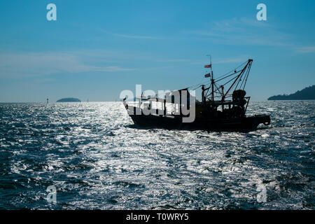 Fishing boats in silhouette on the South China Sea with a sun spike, reflection in Kota Kinabalu, Sabah, Borneo, Malaysia. - Stock Photo