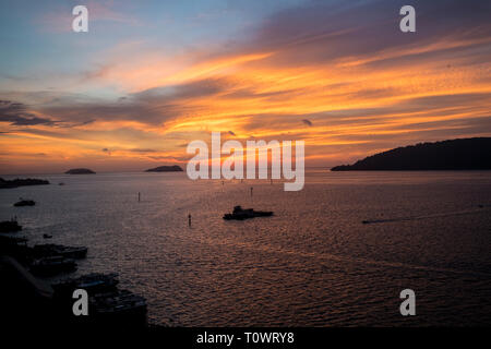 A stunning, beautiful, orange sunset over the South China Sea in Kota Kinabalu, Sabah, Borneo, Malaysia. - Stock Photo