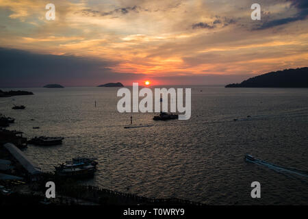 A stunning, beautiful, orange sunset with sun ball over the South China Sea in Kota Kinabalu, Sabah, Borneo, Malaysia. - Stock Photo